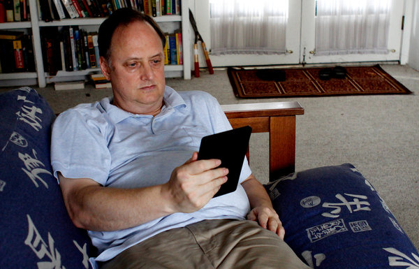 "Reading a book on a tablet like the Kindle Fire is ""like trying to cook when there are little children around,"" David Myers said. 