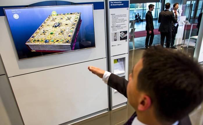 Um visitante testa um visualizador de livros 3D no estande da no Fraunhofer na feira tecnológica Cebit, que acontece até este sábado [9] em Hannover, na Alemanha